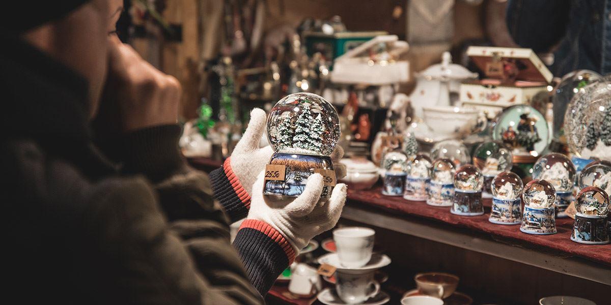 Shopper admiring snow globe at a Christmas market