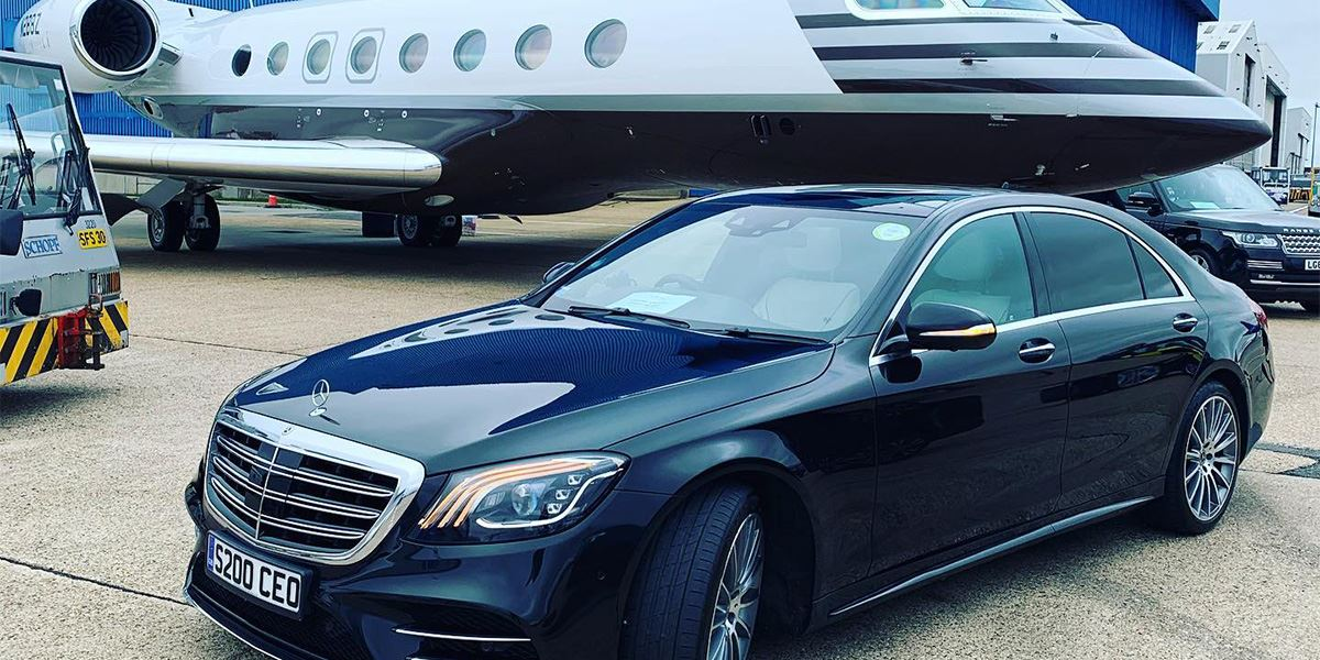 A Jonny-Rocks luxury Mercedes-Benze S-Class saloon stands in front of a private jet