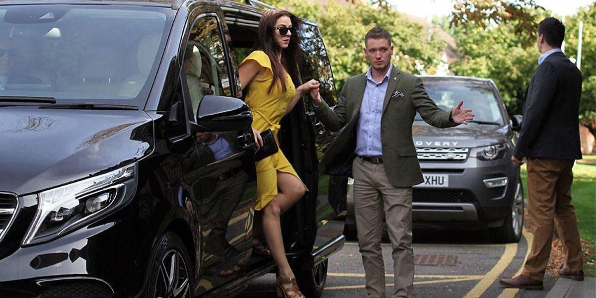 A Jonny-Rocks chauffeur assists a VIP from a Mercedes-Benz V-Class MPV