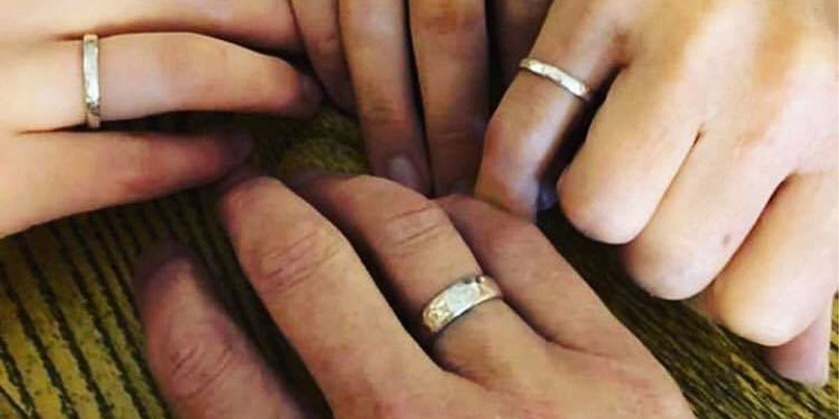 A group of four friends show off their hand-forged rings together