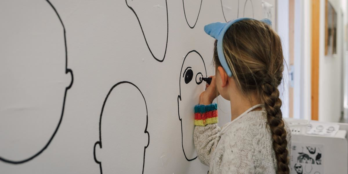 Girl drawing a face at Artists Open Houses, Brighton