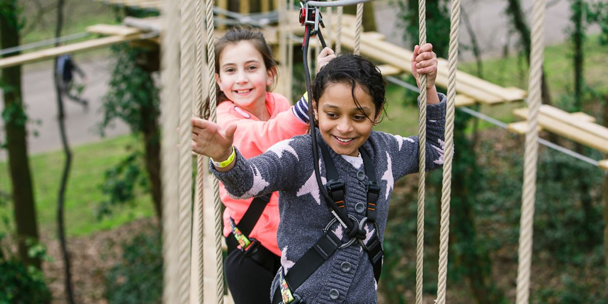Two girls crossing the rope ladders at Go Ape