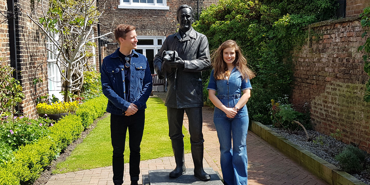 A man and a woman stand next to a statue of vet james Alfred Wight at The World of James Herriot